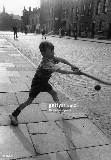 A young boy playing an improvised game of cricket with a bat and ball in an English street Original Publication Picture Post 7230 Children Of The...