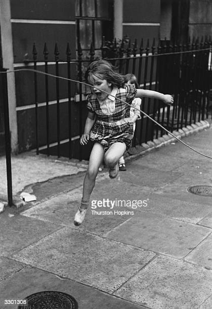 A young girl skipping on a city pavement with a rope tied to some railings Original Publication Picture Post 7230 Children Of The Streets pub 1954