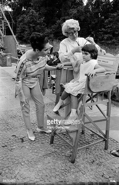 American film actress Elizabeth Taylor looks on as her daughter Liza Todd has her hair combed by a hairdresser on the set of 'Becket' at Shepperton...