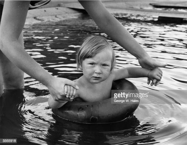 Two year old Abigail Sterne enjoys a bathe at the Serpentine Lido Hyde Park London with the assistance of her mother and an innertube