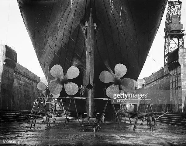 Workers removing barnacles from the propellers of the Royal Navy training ship Majestic at Southampton. The vessel, which started out as the...