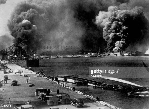 General view of Pearl Harbour after it had been attacked by the Japanese. Smoke pours from USS Shaw whilst the minelayer USS Oglana lies capsized in...
