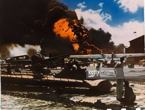 Black clouds of smoke pour from aircraft ablaze on a military airfield near Pearl Harbour , Oahu Island after a surprise attack by the Japanese which...