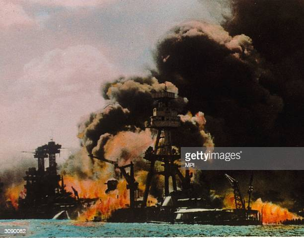 Black smoke and flames pour out of a battleship on fire in Pearl Harbour Oahu Island after a surprise attack by the Japanese which brought America...