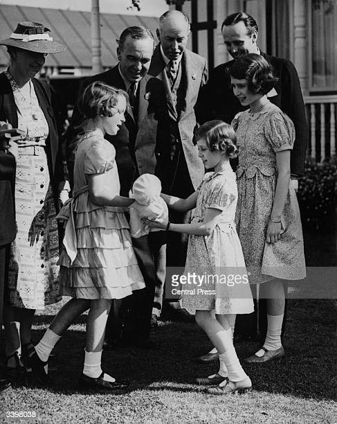 Princess Elizabeth watching Princess Margaret receive a presentation doll on behalf of elementary school girls during a ceremony in Windsor Great...
