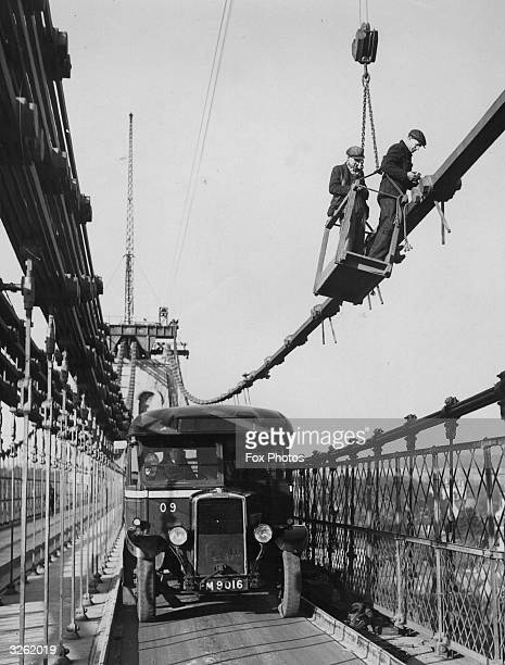 Thomas Telford's Menai Suspension Bridge between mainland Wales and Anglesey is supported by two cables during repairs.