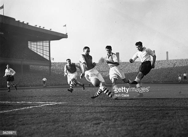 Tottenham Hotspur forward Len Duquemin shoots at goal despite the efforts of the Arsenal defence in a North London derby at Highbury