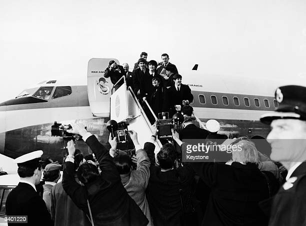 Press photographers scramble for the best pictures as British pop group The Beatles depart from London Airport bound for America