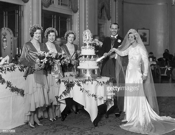 Dancer Audrey Tosh of The Tosh Twins and her husband George Thomas cutting their wedding cake beside their bridesmaids sisters Iris Esme and Natalie...
