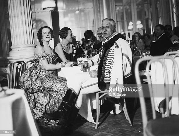 From left to right Mrs WooleyHart Mrs Pryce Harrison and Mr Hugh Fraser attend the Strauss Ball at the Savoy Hotel in London The ball proceeds of...
