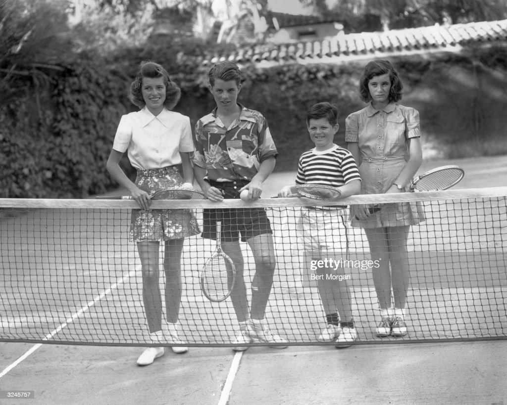 Eunice, Robert, Ted, and Jean Kennedy smile as they stand behind the net on the tennis court at the Kennedy ocean front home in Palm Beach, Florida.