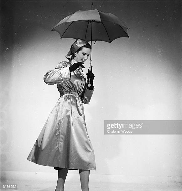 A belted raincoat buttoned to the waist worn with a turban style hat in the same material