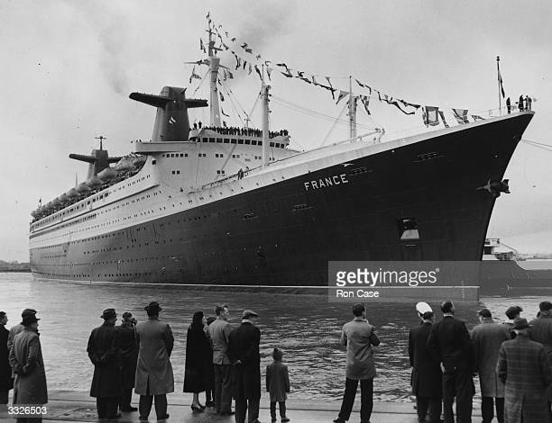 People on the quayside watch as the new 1035 ft French passenger liner 'France' manoeuvres out of the Ocean Terminal at Southampton on her way home...