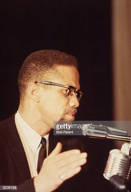 Profile portrait of American civil rights leader Malcolm X gesturing while speaking into microphones