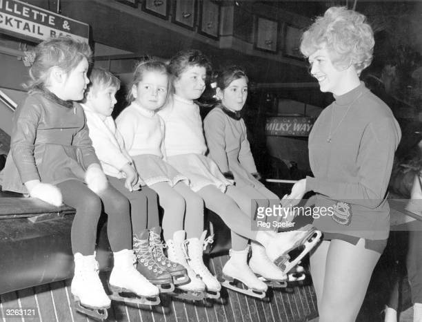 Ice Dance gold-medallist and skating instructress Sylvia Coe checks the skates of young skaters before a lesson at the Silver Blades Ice Rink at...