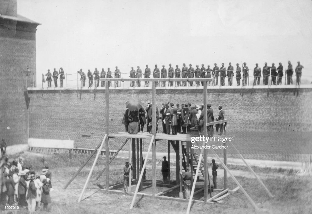 Full-length view of President Abraham Lincoln's assassins, wearing hoods over their heads, sitting on the gallows prior to their execution, Washington. Union soldiers preside over the hangings while other soldiers watch from the wall of the fortified compound. The conspirators were Mrs. Surratt, Lewis Payne, David Herold, and George Atzerodt.
