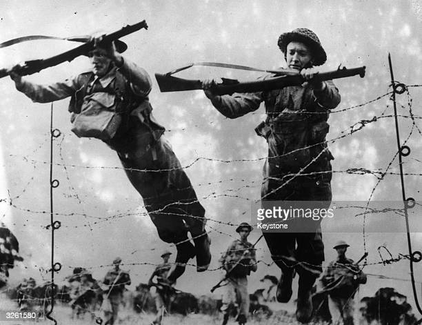 Australian soldiers throw themselves onto barbed wire during training to let other troops pass over more comfortably