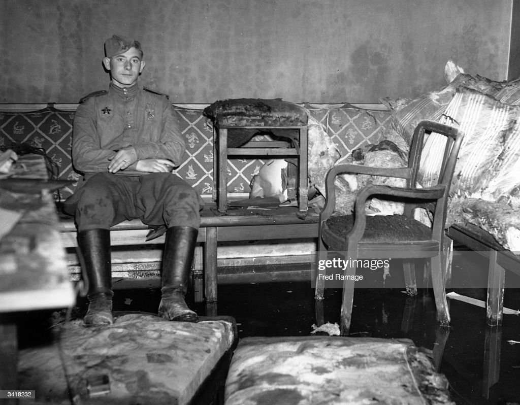 A Russian soldier sitting on the sofa upon which German dictator Adolf Hitler is reported to have killed himself, in Hitler's shelter under the Chancellery, Berlin.