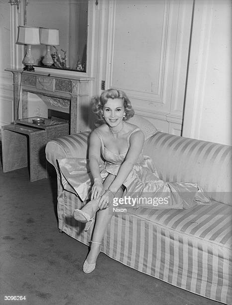Film star Zsa Zsa Gabor wife of George Sanders poses on a striped sofa