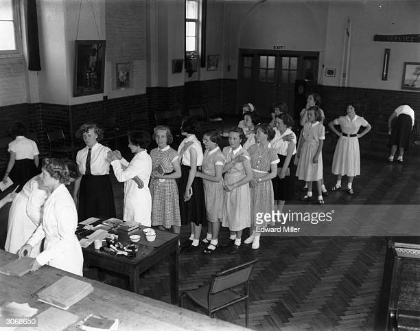 Schoolgirls queue for TB vaccinations, during a mass vaccination carried out at the Kilmorie Secondary school, London SE 23, performed by Dr M....