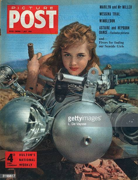 French starlet Isabelle Corey leans on one of Monsieur Robikoff's underwater photographic torpedoes on the beach at Cannes and on the cover of...