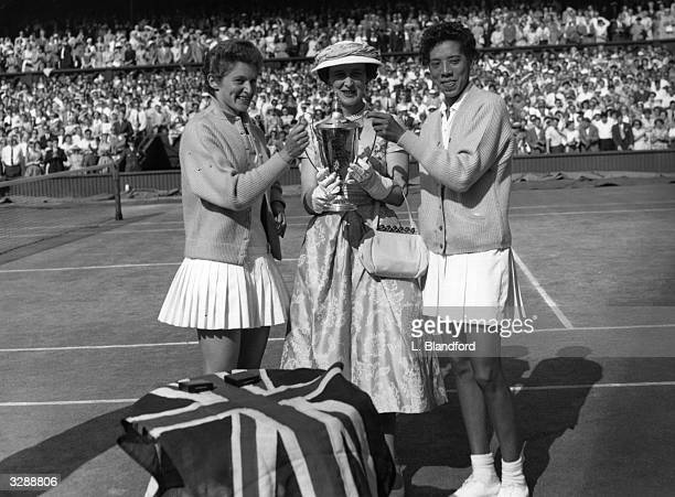 The Duchess Marina of Kent presenting the trophy to Angela Buxton and Althea Gibson after their victory in the women's doubles at the Wimbledon Lawn...