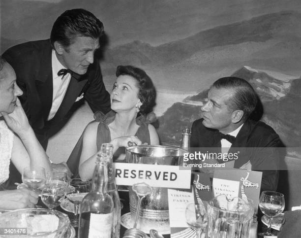 Actor Kirk Douglas talks to Lord and Lady Olivier British actress Vivien Leigh at the Mayfair Hotel