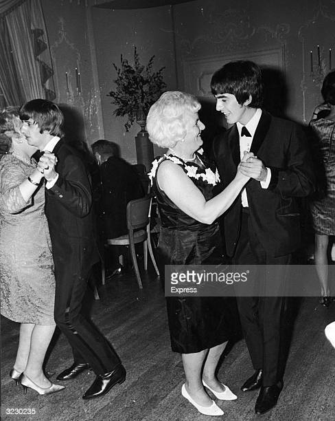 British musicians George Harrison and Ringo Starr members of the rock group The Beatles dance with their mothers at the premiere party for their film...