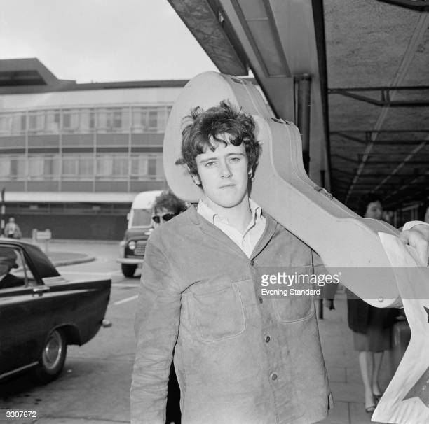 British folkpop singer songwriter Donovan Leitch better known as Donovan carrying his guitar on his shoulder