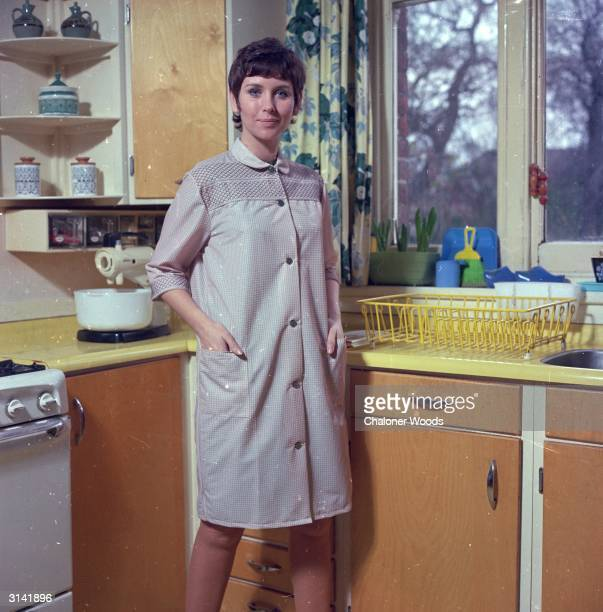 A housewife wearing cleaning overalls stands in her colourful kitchen ready to face the chores of the day