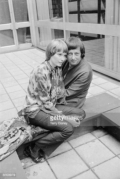 American actress Mia Farrow and husband, German-born composer and London Symphony Orchestra conductor Andre Previn share a low bench on a tiled floor.