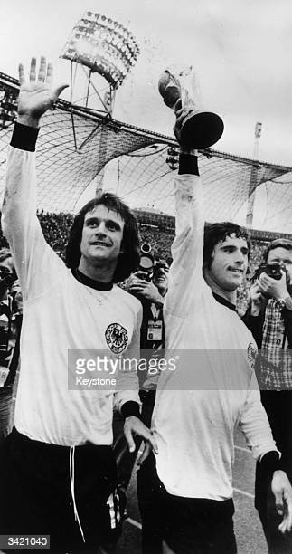 West German footballer Gerd Muller holds the World Cup aloft as he performs a lap of honour with his team mate Overath after beating Holland 21 in...