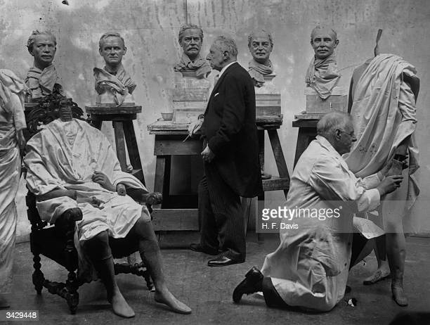 John Tussaud of the famous waxworks Madame Tussaud's working on the 'big five' the leading statesmen of the Socialist Government Left to right Joseph...