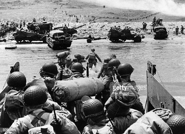 American assault troops and equipment landing on Omaha beach on the Northern coast of France, the smoke in the background is from naval gunfire...