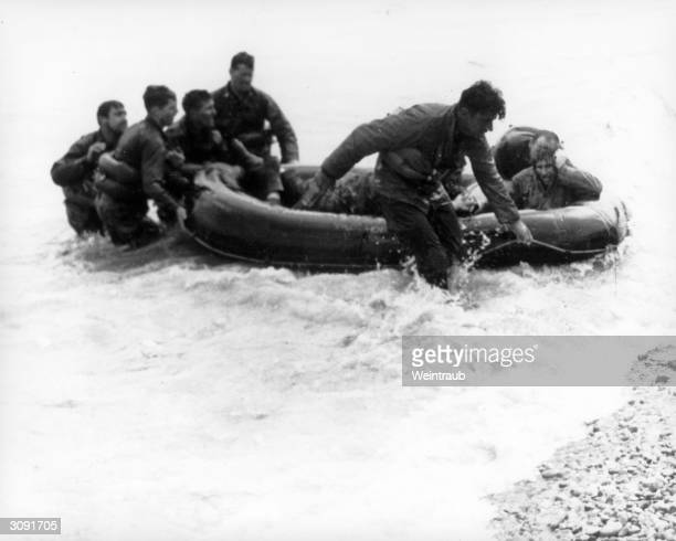 American troops come ashore at Omaha Beach in a liferaft after their Landing Craft VehiclePersonnel had been sunk off the Beachhead