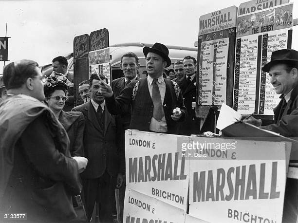 Punters crowd around the Jack Marshall bookmaker's stand at Epsom on Derby day