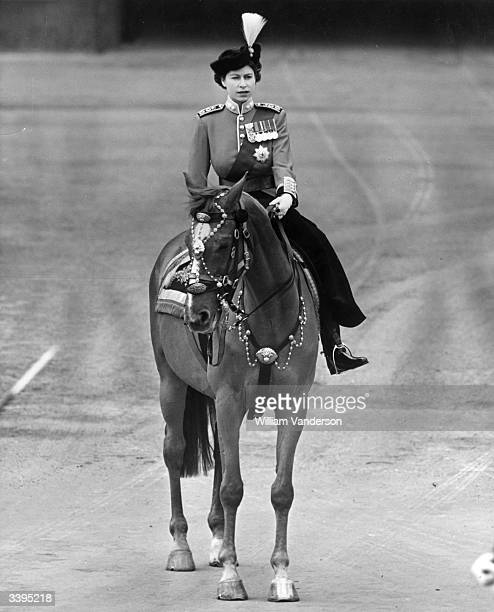 Princess Elizabeth II riding side saddle during a Trooping the Colour ceremony at Horse Guard's Parade London