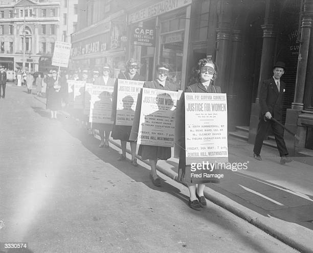 A group of masked women wearing sandwichboards advertising a meeting calling for equal pay rights for women to be held at Central Hall England