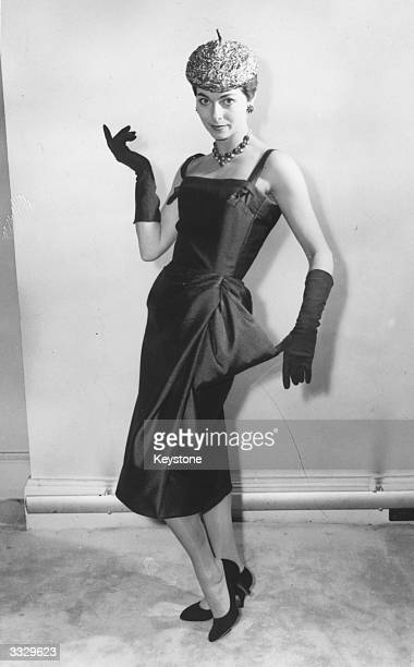 Model Avril Humphries modelling 'Mayfair' a sheath dress in bronze wool with gold thread with its skirt draped from the hip at a showing of Christian...