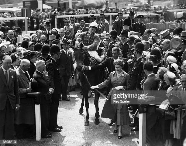 Queen Elizabeth II of Great Britain leads her horse 'Carrozza' and its jockey Lester Piggott into the winner's enclosure at the Epsom racecourse...