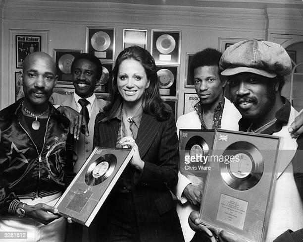 Author Jackie Collins presenting pop group Hot Chocolate with silver discs for the sales of their single 'Emma' number two in the British charts The...