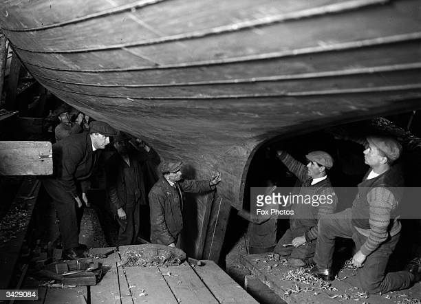 Workmen smoothing down the hull of the sailing ship Shamrock before her entry into the America's Cup.