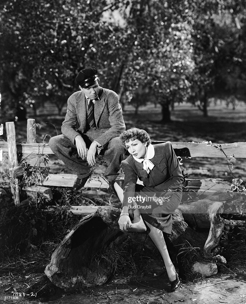 French actress Claudette Colbert (1903 - 1996) complains of sore feet in a scene from W S Van Dyke's screwball comedy 'It's a Wonderful World', while her co-star James Stewart (1908-1997) sits on the fence.