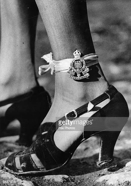 A woman wearing a regimental badge tied to her ankle with a bit of ribbon