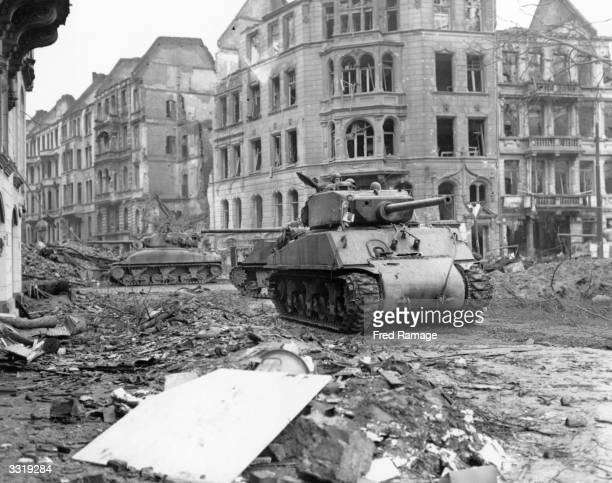 Tanks of the 3rd Us Army rumble down the debris littered streets of Cologne with gutted buildings in the background