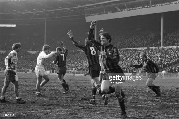Manchester City's right half Mike Doyle and his team mates Colin Bell and G Heslop celebrate Doyle's equalising goal at Wembley against West Bromwich...