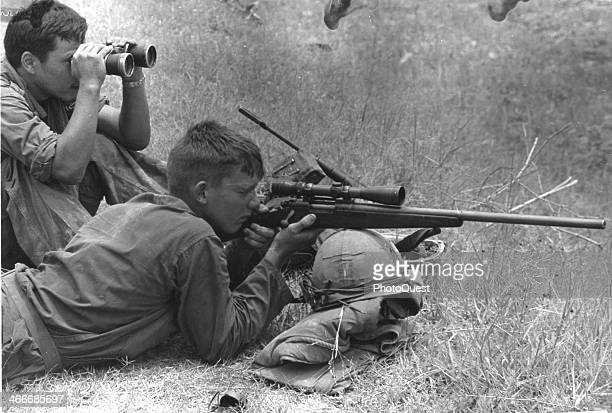 A 7th Marine Regt sniper zeroes in on a distant enemy with his Remington 700 sniper rifle while his companion watches through binoculars Da Nang...