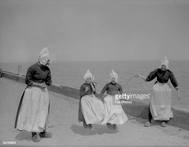 A group of Dutch children playing with a skipping rope by the sea in Volendam near Edam in the western Netherlands