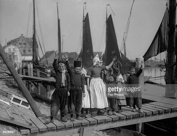 A group of Dutch children waving from a jetty in Volendam near Edam in the western Netherlands
