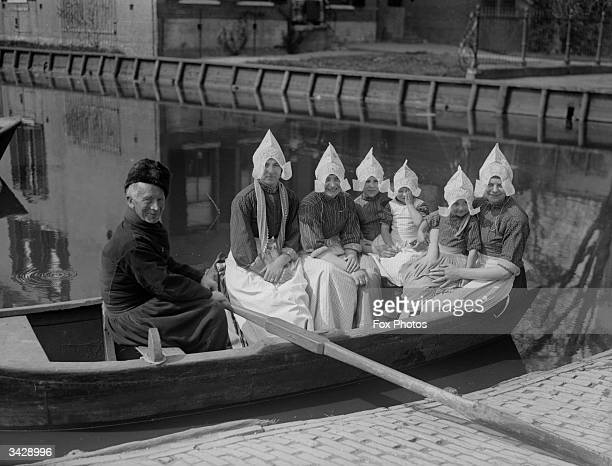 An old boatman takes a group of Dutch ladies for a quiet row at Volendam near Edam in the western Netherlands